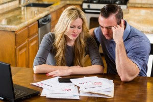 A man and woman overwhelmed with past-due bills and debt.